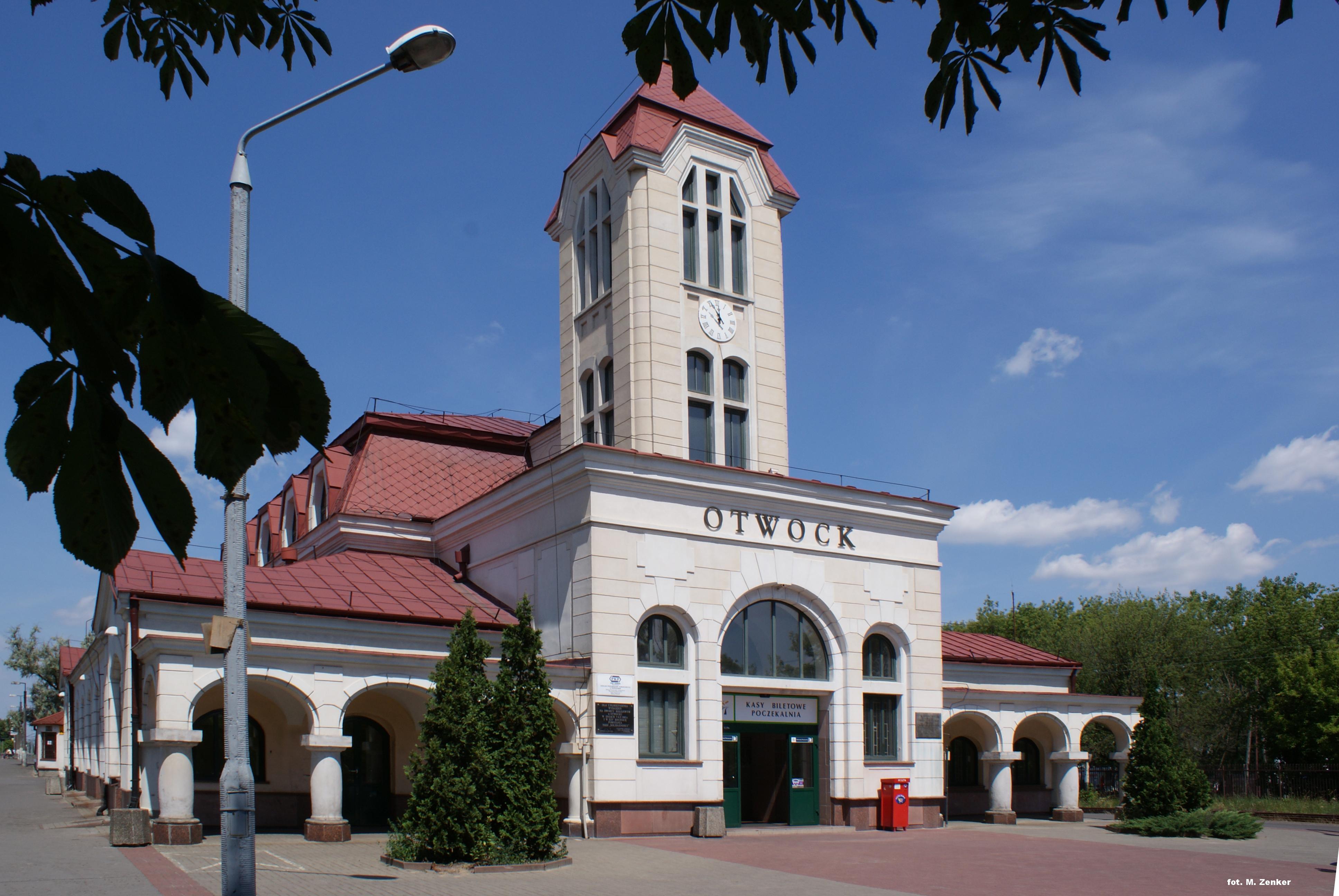 Dworzec kolejowy w Otwocku. Jany budynek z wieżą z zegarem i bordowym dachem. Nad drzwiami wejściowymi tekst Otwock.  Z prawej strony budynku zielone drzewa, w tle niebieskie niebo z białymi chmurami.