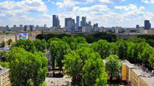 Widok na wieżowce, zielone drzewa, w tle niebieskie niebo z białymi chmurami.
