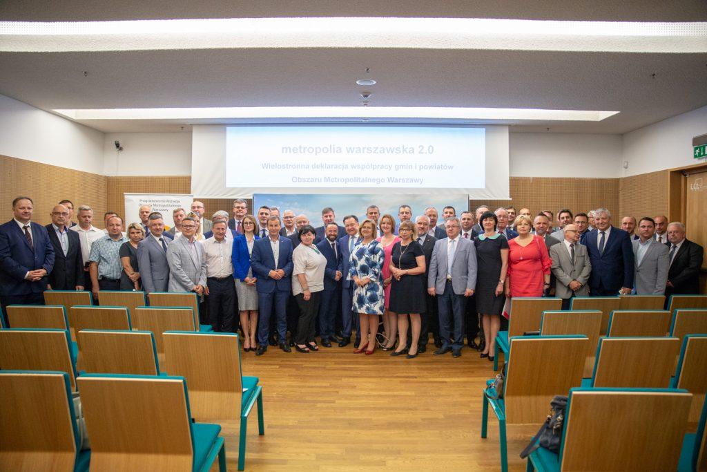 Zdjęcie samorządowców podczas podpisania wielostronnej deklaracji współpracy. Sala konferencyjna, ludzie stoją przed prezentacją, w tle na slajdzie wyświetla się tekst Metropolia 2.0