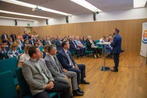 Prezentacja Zastępcy Prezydenta Michała Olszewskiego, po lewej publiczność słuchająca wystąpienia
