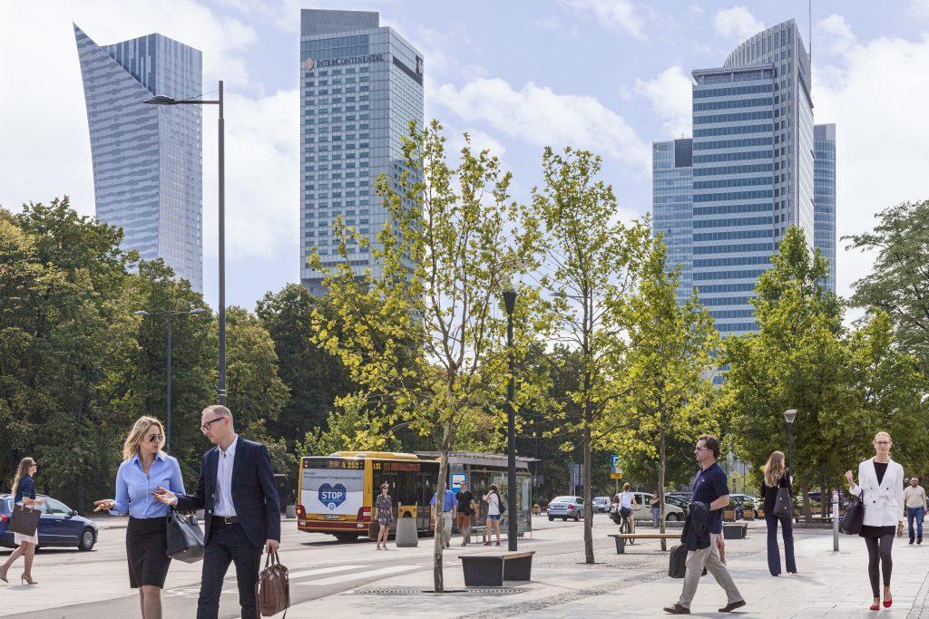 Na zdjęciu wieżowce w Warszawie, drzewa, przystanek autobusowy, ludzie którzy idą i rozmawiają