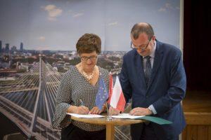 Dwie osoby kobieta i mężczyzna podpisujący umowę, w tle zdjęcie Warszawy
